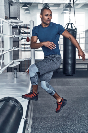 Working out. Handsome young African man in sport clothing jumping while exercising in the gym Stock fotó