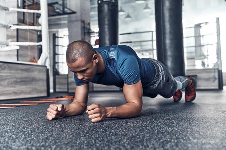 Elke dag routine. Knappe jonge Afrikaanse man in sportkleding planking tijdens het sporten in de sportschool Stockfoto