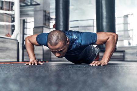 Hard duwen. Knappe jonge Afrikaanse man in sportkleding die opdrukoefeningen doet terwijl het uitoefenen in de gymnastiek Stockfoto