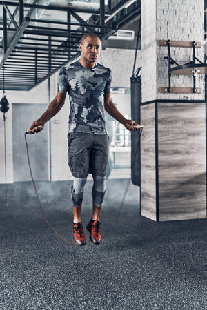 Achieving best results. Full length of young African man in sport clothing skipping rope while exercising in the gym