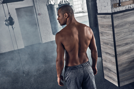 Every day filled with sport. Rear top view of shirtless young African man resting while standing in the gym Stock fotó