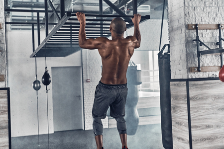 Training to become the best. Rear view of shirtless young African man doing pull-ups while exercising in the gym