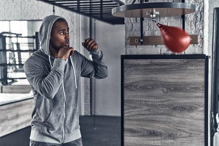 Niets dan succes. Knappe jonge Afrikaanse man in sportkleding boksen tijdens het sporten in de sportschool Stockfoto