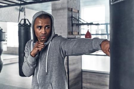 Trainen voor de grote dag. Knappe jonge Afrikaanse man in sportkleding boksen tijdens het sporten in de sportschool Stockfoto