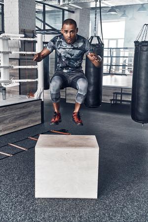 Geef nooit op. Knappe jonge Afrikaanse man in sportkleding springen tijdens het sporten in de sportschool