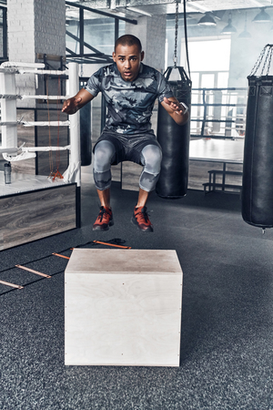 Never give up. Handsome young African man in sport clothing jumping while exercising in the gym Banco de Imagens