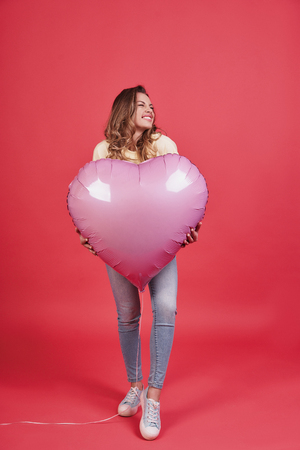 In a mood for a big holiday.   Full length of playful young woman holding heart shaped balloon and smiling while standing against pink background