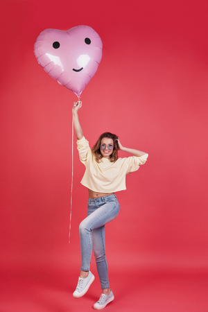 Let the party started!   Full length of attractive young smiling woman holding heart shaped balloon and keeping hand in hair while standing against pink background Standard-Bild - 96827267