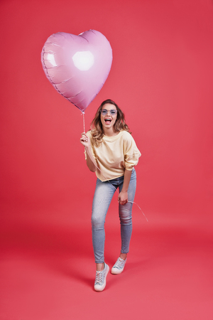 Feeling free to do anything. Full length of attractive young smiling woman holding heart shaped balloon and shouting while standing against pink background