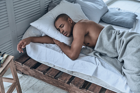 Relaxing at home. Top view of young African man sleeping while lying in the bed at home