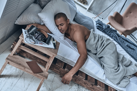 Lost in a deep sleep. Top view of young African man sleeping while lying in the bed at home Stock Photo