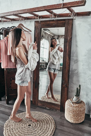 Effortless beauty.  Full length of attractive young woman taking on the blouse and smiling while standing in front of the mirror at home