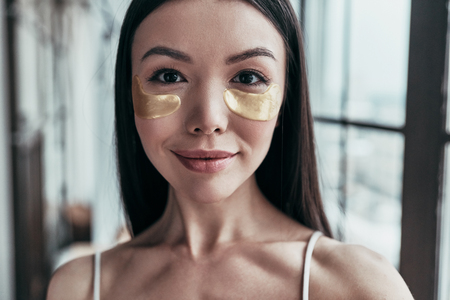 Taking care of her skin. Attractive young woman using eye patches and looking at camera while spending time at home Stock Photo