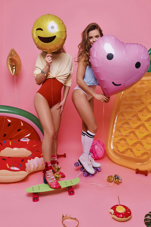 Spending carefree time. Full length of two young women in swimwear covering faces with balloons while standing against pink background