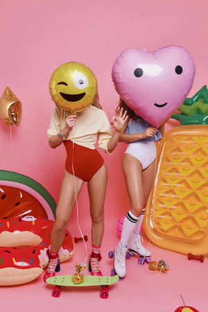 Let the party started! Full length of two young women in swimwear covering faces with balloons while standing against pink background Standard-Bild - 97191108