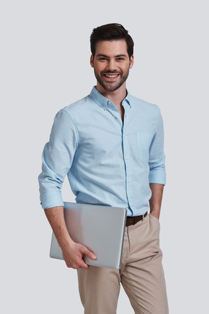 Confident businessman.  Good looking young man carrying laptop and looking at camera with smile while standing against grey background 版權商用圖片