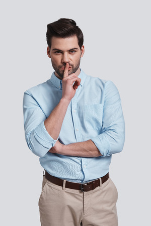 Can you keep a secret?  Handsome young man keeping index finger on lips and looking at camera while standing grey background