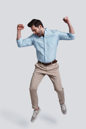Always winning.  Full length of handsome young man gesturing and shouting while jumping grey background Archivio Fotografico - 97274715