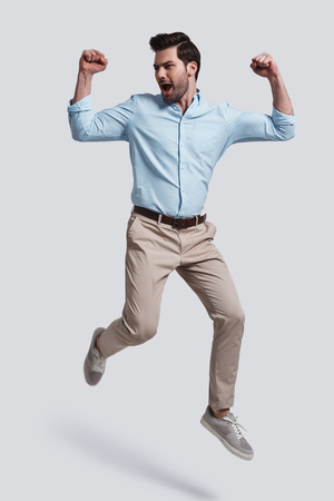 I did it!  Full length of handsome young man gesturing and shouting while jumping grey background