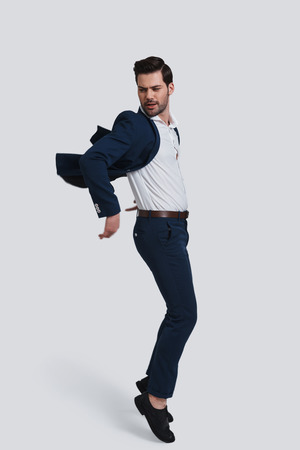 Feeling free to do anything. Full length of handsome young man in full suit making a face while jumping against grey background Stock Photo