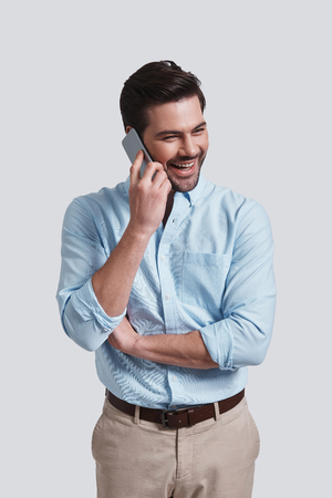 I can totally make it work.  Good looking young man talking on smart phone and smiling while standing against grey background