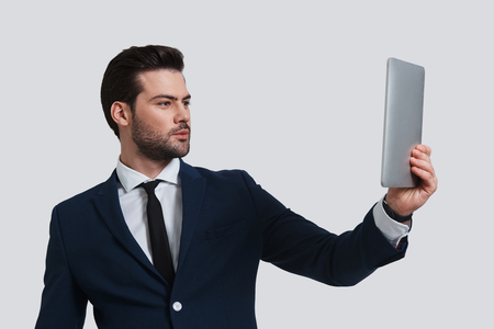 Hi! Good looking young man in full suit holding digital tablet and looking at it while standing against grey background