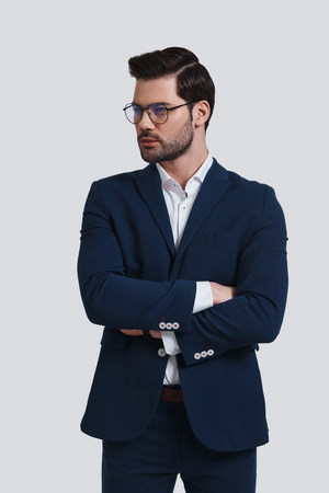 Young and successful. Handsome young man in full suit keeping arms crossed and looking away while standing against grey background