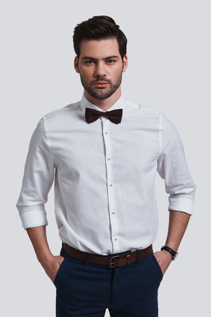 Perfect in every way. Good looking young man looking at camera and keeping hands in pockets while standing against grey background