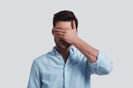 See nothing.  Handsome young man covering eyes with hands while standing grey background