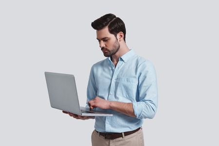 Concentrated at work.  Good looking young man working on his laptop while standing against grey background