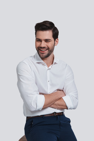 Cheerful and handsome. Good looking young man keeping arms crossed and looking away while sitting against grey background Banque d'images
