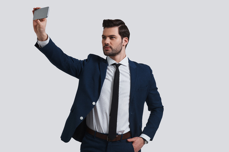 Perfect selfie. Good looking young man in full suit talking selfie using smart phone while standing against grey background Banque d'images