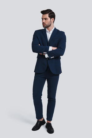 Perfect in his style. Full length of handsome young man in full suit looking away and keeping arms crossed while standing against grey background