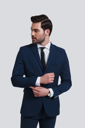 Confidence and charisma. Handsome young man in full suit adjusting sleeve and looking away while standing against grey background Stock Photo