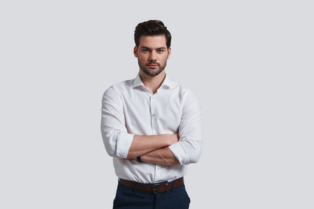 Pure perfection. Good looking young man looking at camera and keeping arms crossed while standing against grey background
