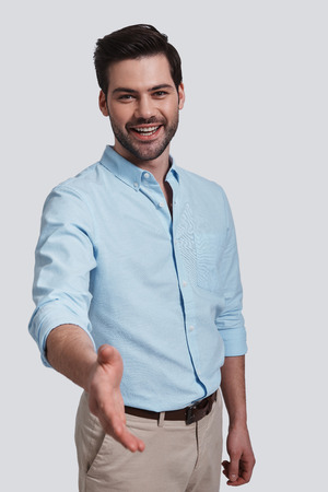 Welcome!  Good looking young man greeting you and smiling while standing against grey background Banque d'images