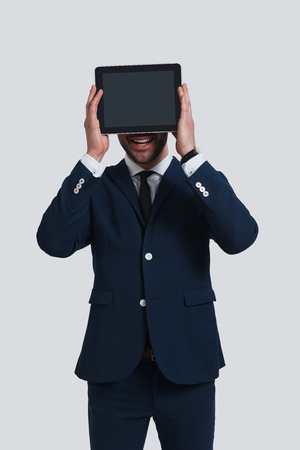 Modern technologies. Good looking young man in full suit covering face with digital tablet and smiling while standing against grey background