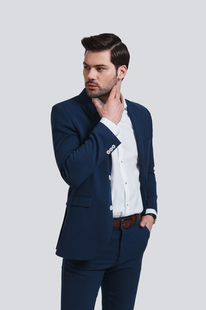 Thinking about solution. Handsome young man in full suit keeping hand in pocket and looking away while standing against grey background