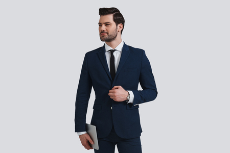 Too good to be real. Good looking young man in full suit adjusting his jacket and looking away with smile while standing against grey background Stok Fotoğraf