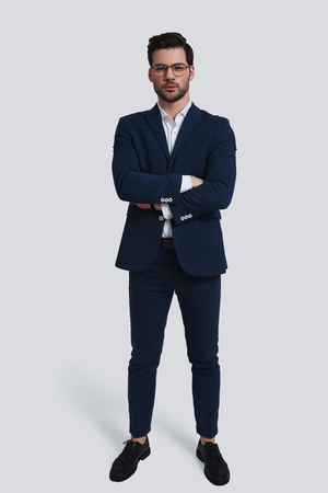 Confident young man. Full length of handsome young man in full suit looking at camera and keeping arms crossed while standing against grey background Banque d'images
