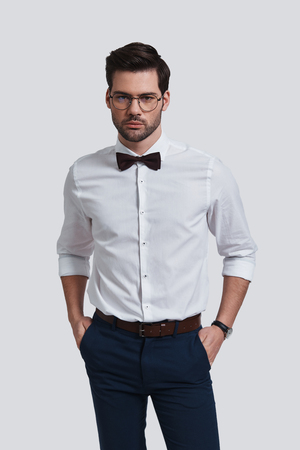 Pure elegance. Good looking young man in eyewear looking at camera and keeping hands in pockets while standing against grey background
