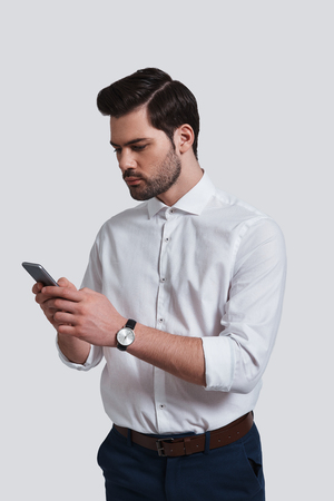 In touch with clients. Good looking young man using his smart phone while standing against grey background