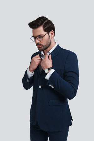 Portrait of confidence. Handsome young man in full suit adjusting his jacket and looking away while standing against grey background