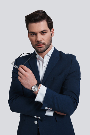 Confident businessman. Handsome young man in full suit holding an eyewear and looking at camera while standing against grey background