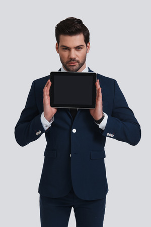 Copy space on his tablet. Good looking young man in full suit holding digital tablet and looking at camera while standing against grey background Banque d'images