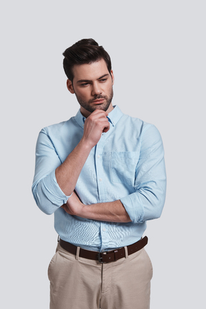 Looking for fresh ideas.  Thoughtful young man looking away and keeping hand on chin while standing against grey background Banco de Imagens - 97275245