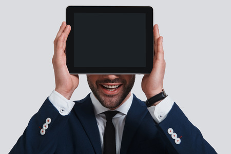 Future is here. Happy young man in full suit covering face with digital tablet and smiling while standing against grey background