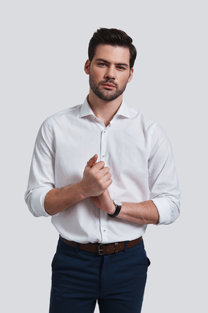 Perfect man. Good looking young man in formalwear keeping hands clasped and looking at camera while standing against grey background