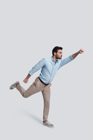 Real hero.  Full length of handsome young man gesturing while standing against grey background Banque d'images