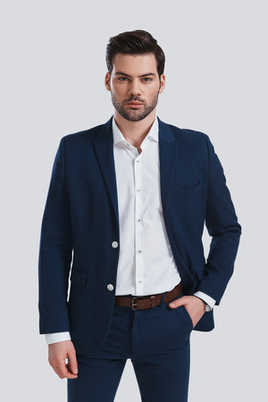 Confident young man. Handsome young man in full suit keeping hand in pocket and looking at camera while standing against grey background Banque d'images